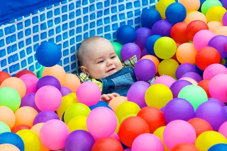 Happy kid playing in the colorful balls photo