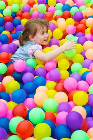 preescolar: Ni�o feliz jugando en las bolas colores