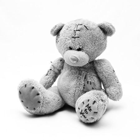 a brown teddy bear with patch on a head sited on white Stock Photo - 7743808