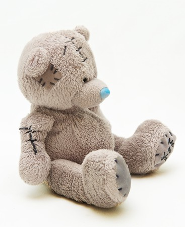 a brown teddy bear with patch on a head sited on white Stock Photo - 7743806