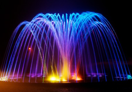 Colored water fountain at night photo