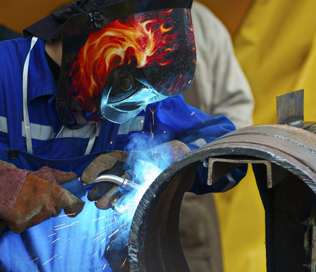 welding worker: Welding pipe for a pipe stand Stock Photo