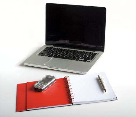 dayplanner: Phone, laptop and empty notebook on the desk Stock Photo
