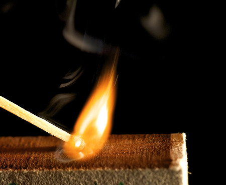 The wooden match is lighted from a box