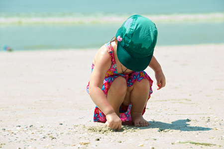 Girl plays on the sand with the toys. Thailand photo