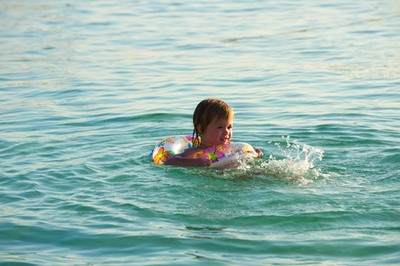The little girl plays in water. photo