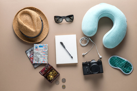 passport background: Packed suitcase of vacation items on wooden table, top view