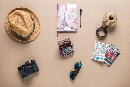objects: Packed suitcase of vacation items on wooden table, top view