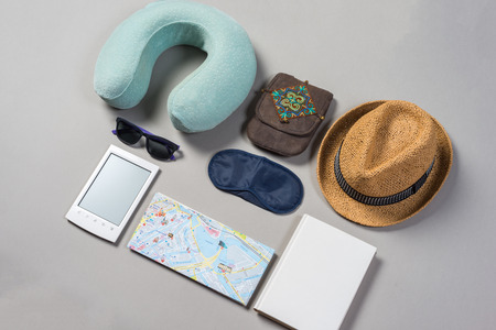 Packed suitcase of vacation items on grey background, top view.
