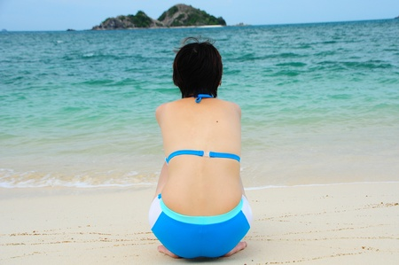 Beautiful young asian woman relaxing at pristine beach photo