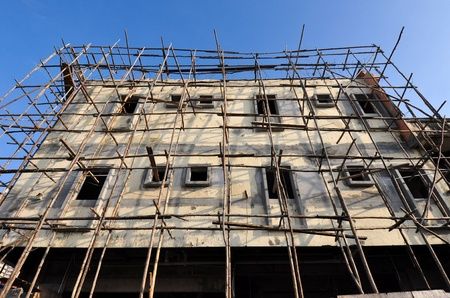Old building reconstruction and renovation with wood scaffolding  photo