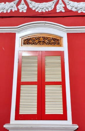 Old wooden window with red color and beautiful craftsmanship of Baba Nyonya style photo