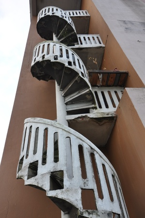 Outdoor old spiral stair case on brown color building photo