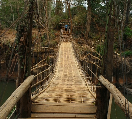 Hanging bamboo bridge over river photo