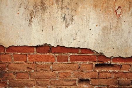 背景のひびの入ったコンクリートのレンガ壁