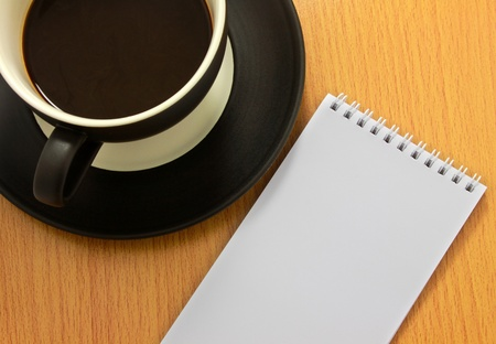Coffee cup and white notebook photo