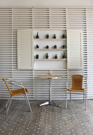 Table and chairs with white wood wall