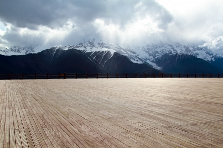 Wood floor with a background of mountains and clouds photo