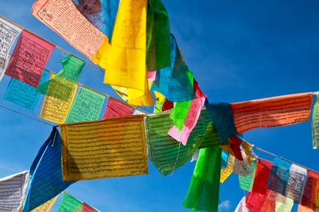 Buddhist tibetan prayer flags flying with blue sky photo