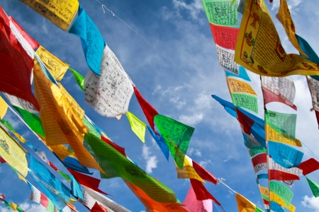Buddhist tibetan prayer flags flying with blue sky 免版税图像