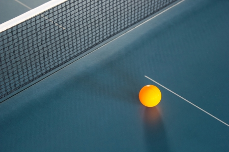 Orange table tennis ball on blue table photo