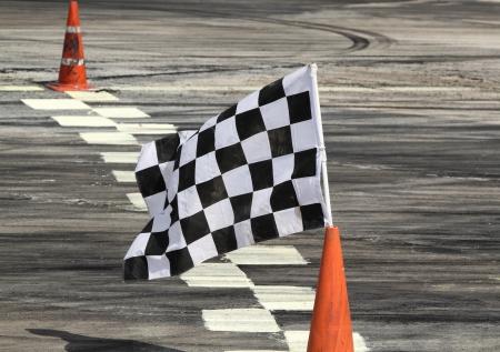 lineas blancas: Finalizar la bandera en la pista en el coche de carreras Foto de archivo