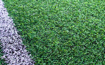 Green artificial grass soccer field for background photo