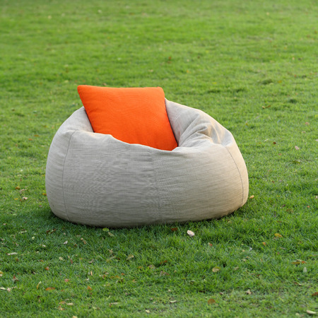 Fabric chair with pillow on green grass photo