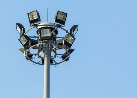 Tall spotlight tower against on blue sky photo
