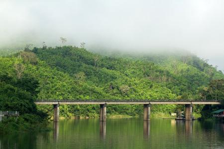 across: Bridge across river with mountain and fog Stock Photo