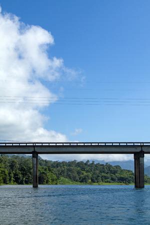 across: bridge across river with mountain blue sky Stock Photo