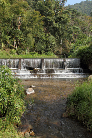 weir: Small weir in valley with water flowing over Stock Photo