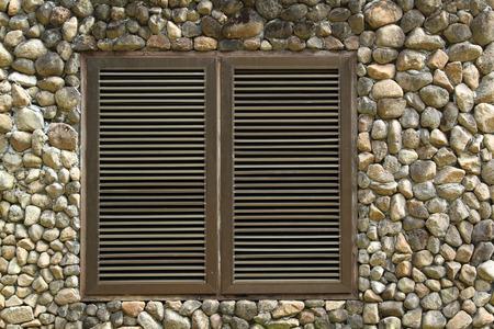 louver: Metal ventilation louver on stone brick wall