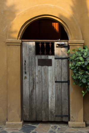 arched: Stucco building with arched and wooden door