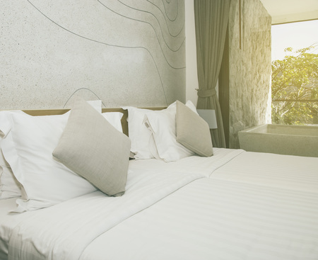 hotel bedroom: Pillows on bed and lamp in bedroom Stock Photo