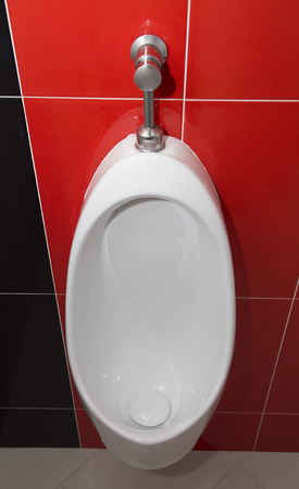 Urinal on tile wall in the restroom Stock Photo