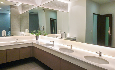 Faucets with washbasin and big mirror in public restroom