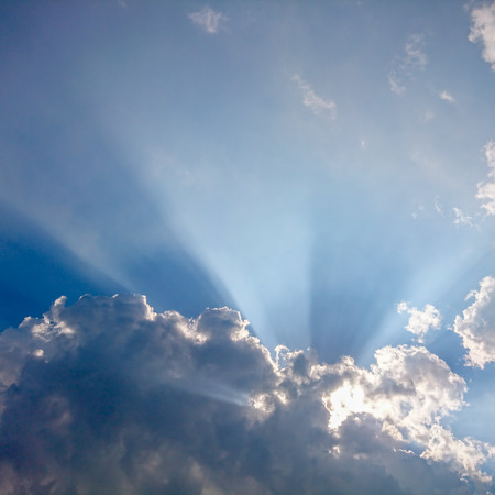 View of clouds in blue sky with rays of light