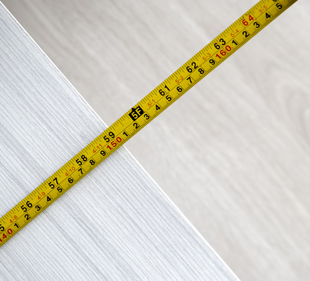 View of tape measure on wooden background