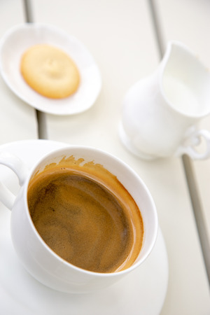 Cup of espresso coffee on white table