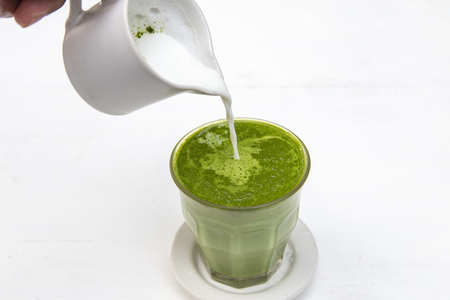 Green tea matcha latte with steam milk on the table