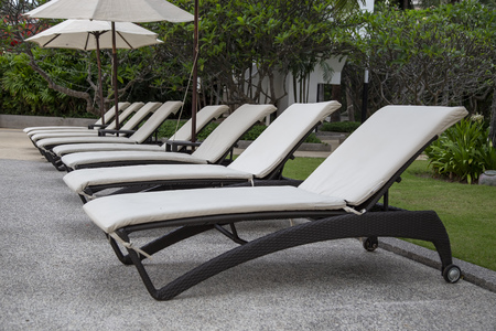 Beach chairs and umbrella beside swimming pool in hotel