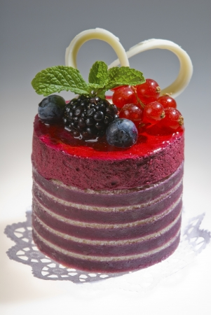 cakes red color of cylindrical form with forest berries,with blackberry  blueberry and red currants