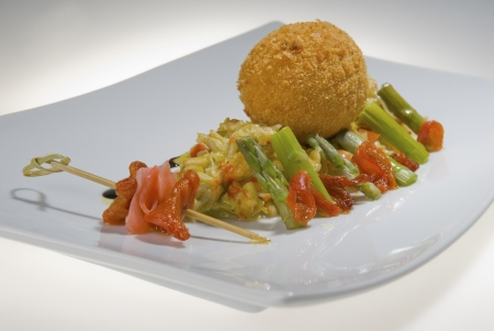 round chicken cutlet with red fish and asparagus on a white rectangular  platter Stock Photo