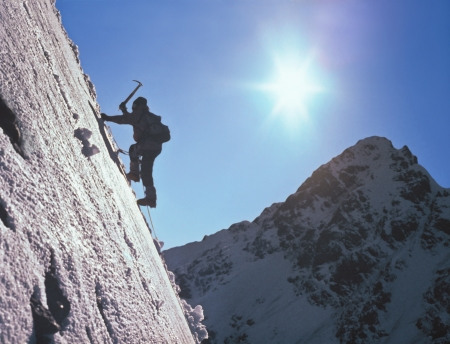 Climber  on ice slope amidst the high mountains and the bright sun Stock Photo