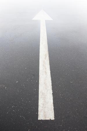 arrow markings  asphalt road leads into  light Reklamní fotografie - 33048831