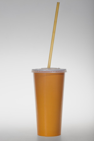 glass of yellow paper with a tube on a white background