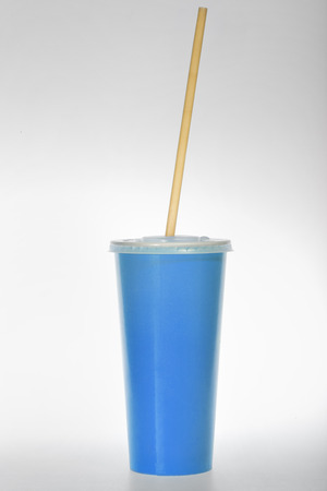 glass of blue paper with a tube on a white background Stock Photo