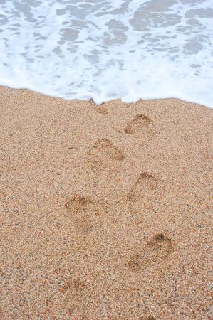 footprints  sand leading into  sea rhythmically stretching