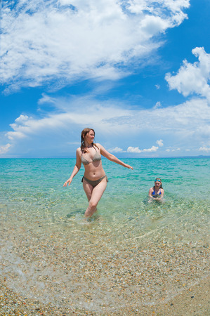 Mother and daughter enjoying time at tropical beach Stock Photo